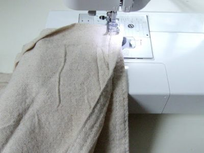 Two pieces of drop cloth being sewn together on a sewing machine