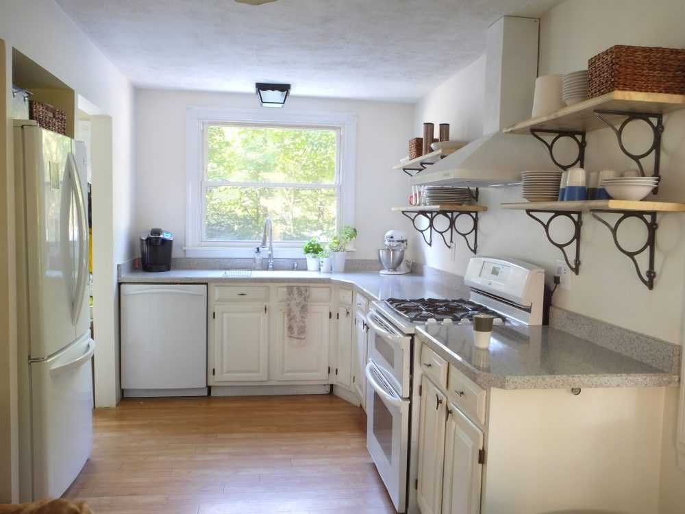 White kitchen cabinets with wall shelves and brackets